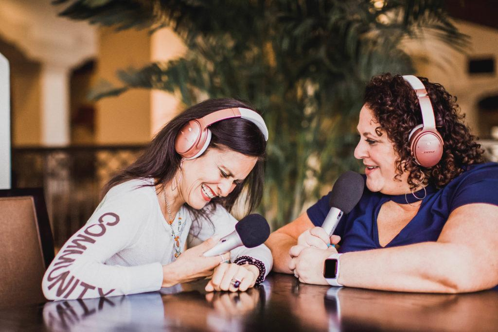 jessica kupferman and elsie escobar laugh while podcasting
